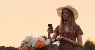 Ragazza abbastanza sveglia che utilizza smartphone accanto alla sua bici nel parco con le palme un giorno soleggiato Ragazza graz stock footage