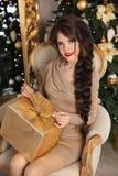 Ragazza abbastanza teenager adorabile con il contenitore di regalo sopra il backgroun di Natale Immagine Stock