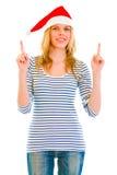 Ragazza abbastanza teenager in cappello della Santa che indica in su fotografia stock libera da diritti
