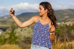 Ragazza abbastanza teenager che prende foto dal telefono Fotografia Stock