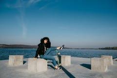 Ragazza abbastanza teenager che spende tempo nel parco vicino all'acqua con il suo pattino Fotografia Stock Libera da Diritti