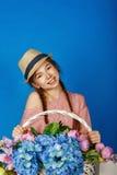 Ragazza abbastanza teenager con un canestro dei fiori Fotografie Stock