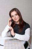 Ragazza in abbigliamento di affari che parla sulla penna di marcatura del telefono con Ne Immagine Stock