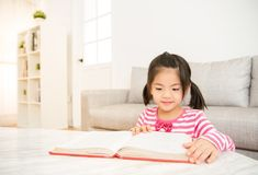 Ragazza abile alla tavola con i libri di lettura Fotografia Stock