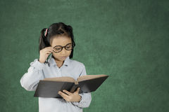 Ragazza abile che legge un libro nell'aula Fotografia Stock