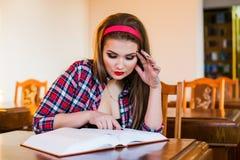 Ragazza abile della coda di cavallo dei capelli della studentessa che si siede nella biblioteca con i libri Fotografia Stock
