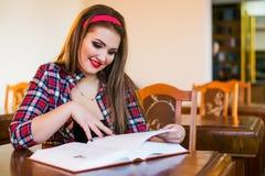 Ragazza abile della coda di cavallo dei capelli della studentessa che si siede nella biblioteca con i libri Immagini Stock