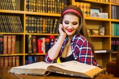 Ragazza abile della studentessa che si siede nella biblioteca con i libri Immagine Stock Libera da Diritti