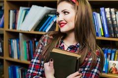 Ragazza abile della studentessa che si siede nella biblioteca con i libri Fotografia Stock