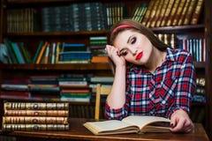 Ragazza abile della studentessa che si siede nella biblioteca con i libri Immagini Stock Libere da Diritti