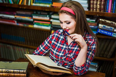 Ragazza abile della studentessa che si siede nella biblioteca con i libri Fotografia Stock Libera da Diritti
