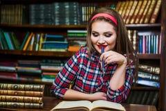 Ragazza abile della studentessa che si siede nella biblioteca con i libri Immagini Stock