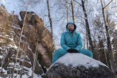 Ragazza in abiti sportivi blu che si siedono su un grande masso sulla natura sui precedenti delle rocce nell'inverno immagini stock libere da diritti