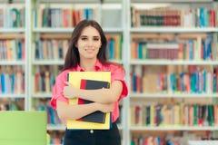 Ragazza accademica che tiene il suoi libro e carte in una biblioteca Immagini Stock