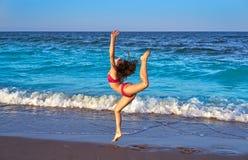 Ragazza acrobatica del bikini di ginnastica in una spiaggia fotografie stock libere da diritti