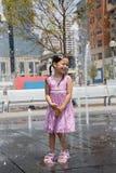 Ragazza ad una fontana della spruzzata Immagini Stock