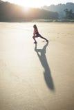 Ragazza adatta che fa rilassamento allungando esercizio alla spiaggia Fotografie Stock Libere da Diritti