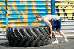 Ragazza adatta con la gomma gigante di tornitura di allenamento del camion più Immagine Stock