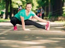 Ragazza adatta dei giovani che allunga per i muscoli della gamba Immagini Stock