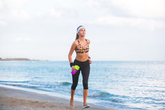Ragazza adatta dei giovani che allunga sulla spiaggia all'alba Fotografia Stock