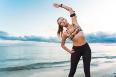 Ragazza adatta dei giovani che fa esercizio di mattina sulla spiaggia all'alba Fotografie Stock Libere da Diritti
