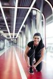 Ragazza adatta giù per fare i laccetti alla palestra di forma fisica prima dell'allenamento corrente di esercizio Fotografia Stock