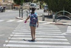 Ragazza adolescente della scuola con uno zaino sul suo indietro e sulle cuffie Fotografia Stock Libera da Diritti