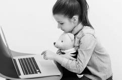 Ragazza adorabile che abbraccia orsacchiotto sveglio e che scrive sul computer portatile immagini stock libere da diritti