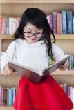 Ragazza adorabile che tiene un libro in biblioteca Immagine Stock Libera da Diritti