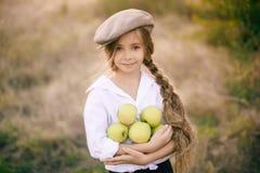 Ragazza adorabile con capelli biondi lunghi intrecciati in una treccia in un cappuccio ed in mele nella campagna fotografia stock libera da diritti