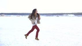 Ragazza adorabile con funzionamento lungo dei capelli al paesaggio di inverno stock footage