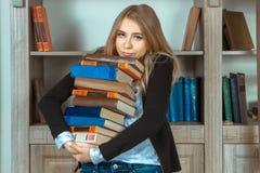 Ragazza adorabile con i grandi libri a disposizione Fotografie Stock