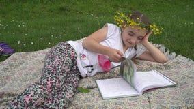 Ragazza adorabile con la corona sul libro di lettura capo Bambino che si trova nell'erba stock footage
