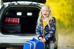 Ragazza adorabile con una valigia pronta a andare sulle vacanze con i suoi genitori Bambino che guarda in avanti per un viaggio s Immagine Stock Libera da Diritti