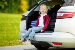 Ragazza adorabile con una valigia pronta a andare sulle vacanze con i suoi genitori Bambino che guarda in avanti per un viaggio s Fotografie Stock Libere da Diritti