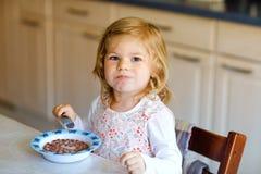 Ragazza adorabile del bambino che mangia cereale sano con latte per il bambino felice sveglio del bambino della prima colazione n fotografia stock libera da diritti