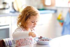 Ragazza adorabile del bambino che mangia cereale sano con latte per il bambino felice sveglio del bambino della prima colazione n immagine stock libera da diritti