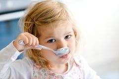 Ragazza adorabile del bambino che mangia minestra dal cucchiaio Bambino felice sveglio del bambino in vestiti variopinti che si s fotografie stock
