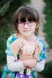 Ragazza adorabile del bambino nella bamboletta degli abbracci di vetro Immagini Stock Libere da Diritti