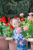 Ragazza adorabile del piccolo bambino in parco vicino al letto di fiore nel giorno di estate Fotografia Stock