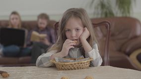 Ragazza adorabile del ritratto piccola che mangia i biscotti che si siedono alla tavola e che esaminano la macchina fotografica F archivi video