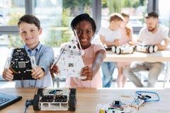 Ragazza adorabile e suo l'amico che posano con i modelli del robot Immagine Stock