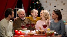 Ragazza adorabile felice che abbraccia i nonni, famiglia che ha cena tradizionale di natale fotografie stock libere da diritti
