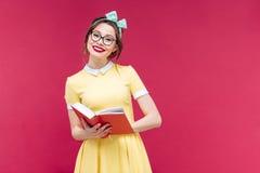 Ragazza adorabile felice del pinup in vetri che legge un libro Fotografia Stock
