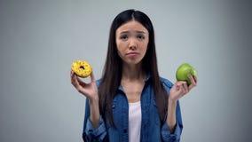 Ragazza affamata che prova a scegliere fra la ciambella e la mela, cibo sano, tentazione immagine stock