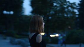 Ragazza affascinante che cammina da solo attraverso la città a tarda sera stock footage