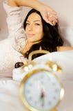 Ragazza affascinante che si sveglia nel pigiama con l'orologio Immagine Stock Libera da Diritti