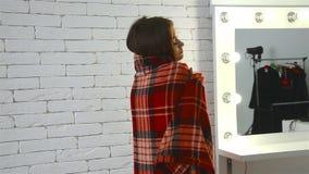 Ragazza affascinante che sta vicino ad uno specchio luminoso e ad una coperta celata archivi video