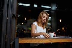 Ragazza affascinante dei pantaloni a vita bassa che aspetta i suoi amici in caffetteria, donna attraente che pensa a qualcosa men Immagine Stock