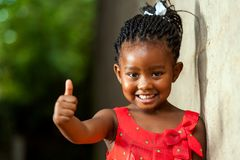 Ragazza africana abbastanza piccola che mostra i pollici su. Fotografia Stock Libera da Diritti